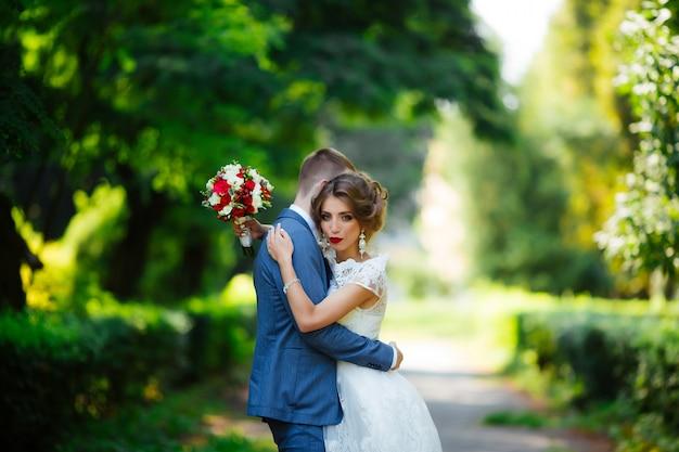Hochzeitspaar, glückliches brautpaar und ehemann, die im grünen park umarmen.
