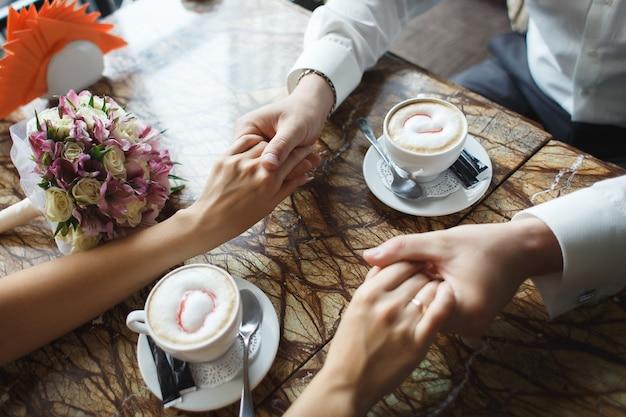 Hochzeitspaar im café. mann hält frauenhand, trinkt cappuccino. braut und bräutigam kaffeepause dating-geschenk, blumenstrauß auf dem tisch.