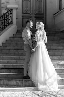 Hochzeitspaar in der stadt am sonnigen sommertag. braut und bräutigam umarmen sich auf der treppe. schwarz und weiß