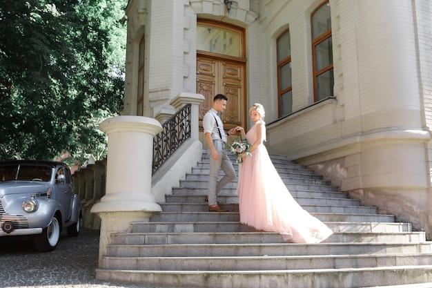 Hochzeitspaar in der stadt am sonnigen sommertag. braut und bräutigam umarmen sich auf der treppe
