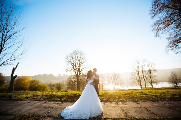Hochzeitspaar in einem wald in den bergen bei sonnenuntergang