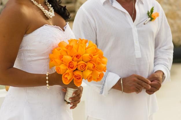 Hochzeitspaar in weiß mit braut, die einen orange blumenstrauß am strand hält. zeremonie, liebesfeierkonzept