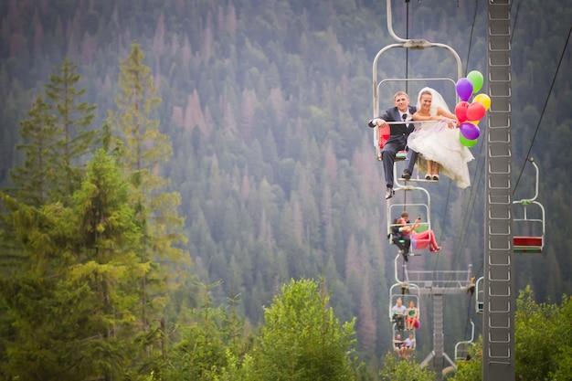 Hochzeitspaar klettert auf einem skilift in die berge