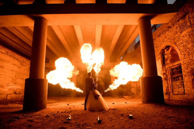 Hochzeitspaar mit schädelgesichtskunst steht in der dunkelheit