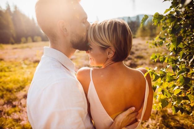Hochzeitspaar umarmt auf dem goldenen feld mit violetten blumen