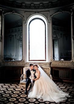 Hochzeitspaar umarmt auf der couch, die vor einem hohen hellen fenster in einer alten luxushalle sitzt