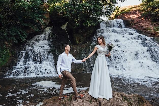Hochzeitspaar umarmt nahe dem gebirgsfluss. bräutigam und braut mit einem blumenstrauß in den händen.