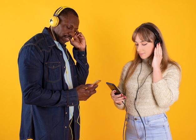 Hochzeitspaar verschiedener rassen, die musik mit kopfhörern und handy hören