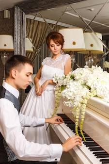 Hochzeitspaare, die auf einem klavier spielen