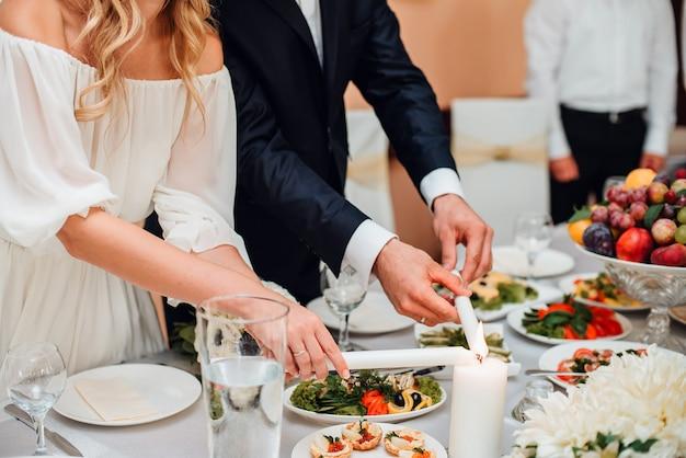 Hochzeitspaare, die candel auf einer tabelle beleuchten