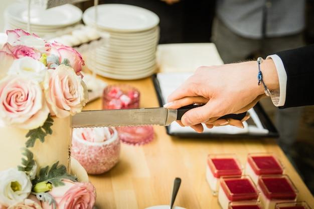 Hochzeitspaare, die die hochzeitstorte an ihrem hochzeitstag schneiden