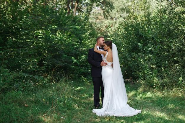 Hochzeitspaare, die draußen romantische momente genießen hochzeitstag im sommer. glückliche emotionale braut und bräutigam, die an einem grünen parkin sonnigen tag geht. bräutigam, der braut küsst. bräutigam umfasst braut im garten
