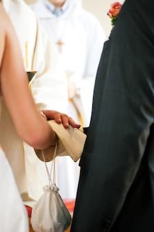 Hochzeitspaare, die segen vom priester empfangen