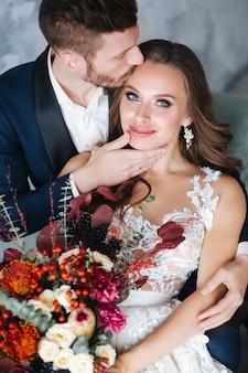 Hochzeitspaare mit der braut, die blumenstrauß hält. sinnliches porträt eines jungen paares. hochzeitsfoto indoor