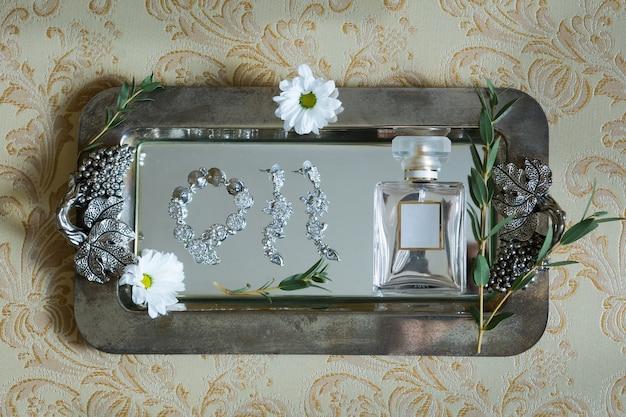 Hochzeitsparfüm, armband, ohrringe auf vintage-hintergrund mit blumen. brautkonzept