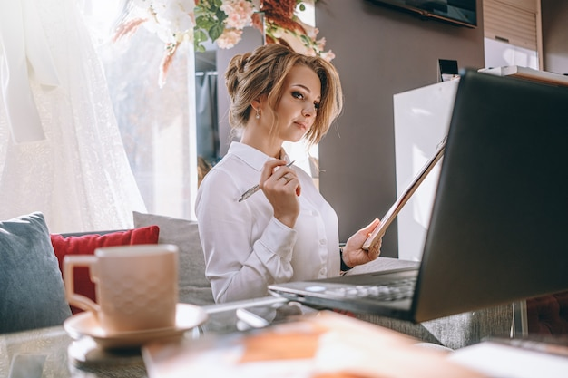 Hochzeitsplaner der jungen frau im büro mit laptop und tablette zum schreiben