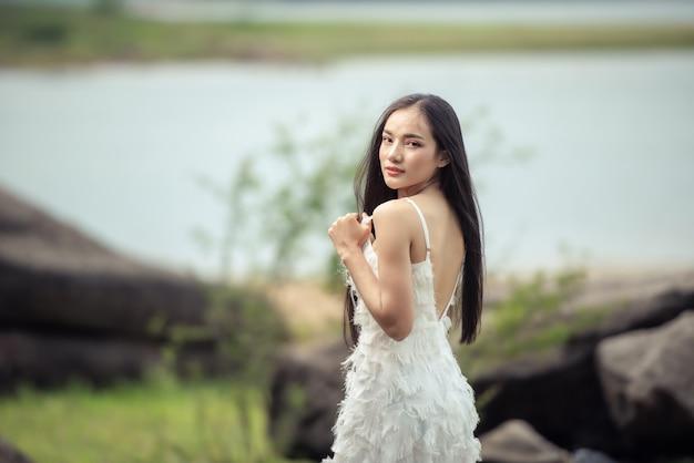 Hochzeitsporträt einer süßen braut asiatischer frau weißes wunderschönes hochzeitskleid vom designer auf dem felsen und im wald, vintage-stil