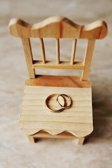 Hochzeitsringe auf einem holzstuhl