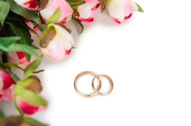 Hochzeitsringe und -blumen getrennt auf weißem hintergrund