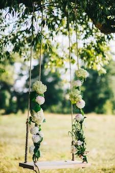 Hochzeitsschaukel verziert mit den blumen, die an den niederlassungen der alten weide hängen