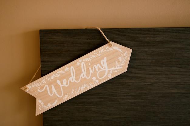 Hochzeitsschild, das an einem hölzernen kopfteil hängt