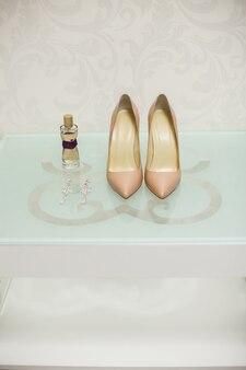 Hochzeitsschuhe cremefarben weiß auf einem glastisch. spirituosen. ohrringe.