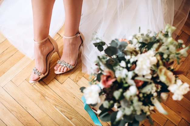 Hochzeitsschuhe der braut mit einem strauß pfingstrosen und anderen blumen.