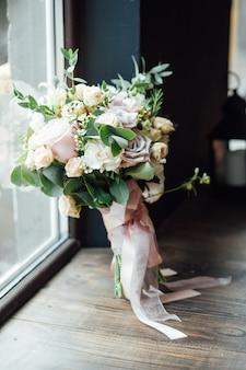 Hochzeitsschuhe mit einem blumenstrauß, der auf dem boden steht.