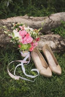Hochzeitsschuhe und ein blumenstrauß im gras.