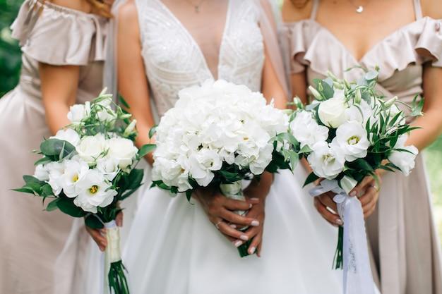 Hochzeitssträuße in den händen der braut und der brautjungfern. weißer hochzeitsstrauß