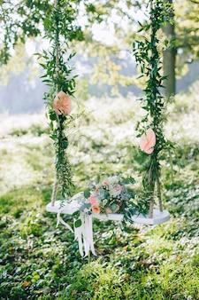 Hochzeitsstrauß aus beigen und rosa rosen im freien auf der dekorierten schaukel