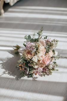 Hochzeitsstrauß aus pfingstrosenblumen auf dem boden des brautpaares