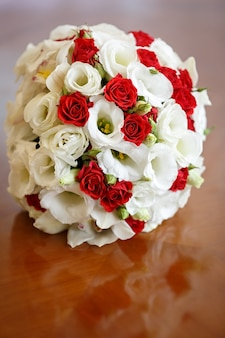 Hochzeitsstrauß aus rosen und lilien auf dem tisch vor dem hintergrund eines hellen fensters.