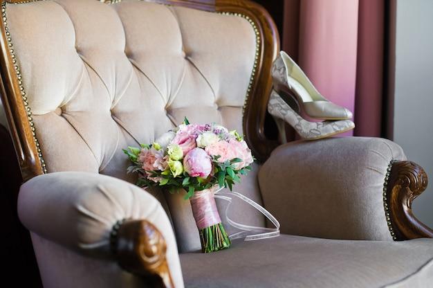 Hochzeitsstrauß aus rosen und pfingstrosen auf einem eleganten klassischen stuhl.