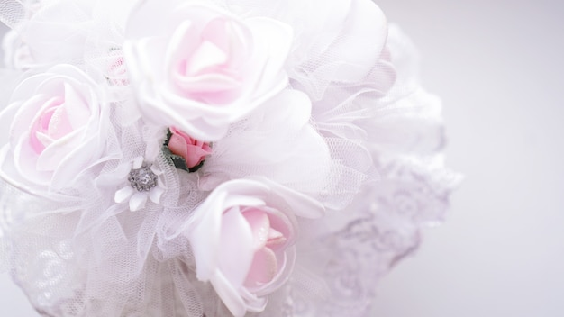 Hochzeitsstrauß aus weißen rosen auf einem verschwommenen weißen hintergrund