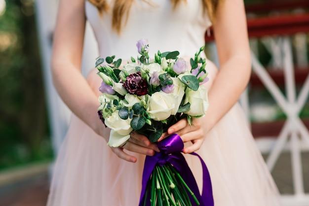 Hochzeitsstrauß aus weißen und violetten rosen in den händen der braut