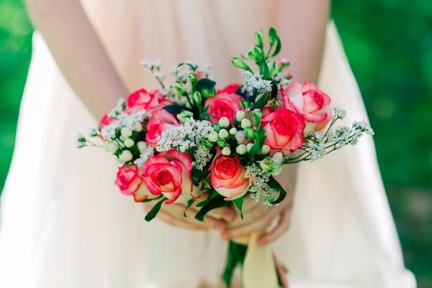 Hochzeitsstrauß der weißen und roten rosen in den händen der braut