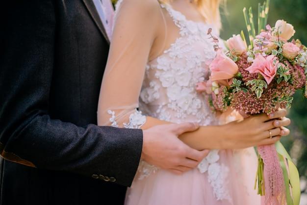 Hochzeitsstrauß in den händen der braut gegen naturhintergrund, nahaufnahme