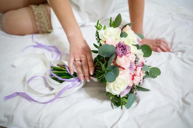 Hochzeitsstrauß in den händen des brautpaares