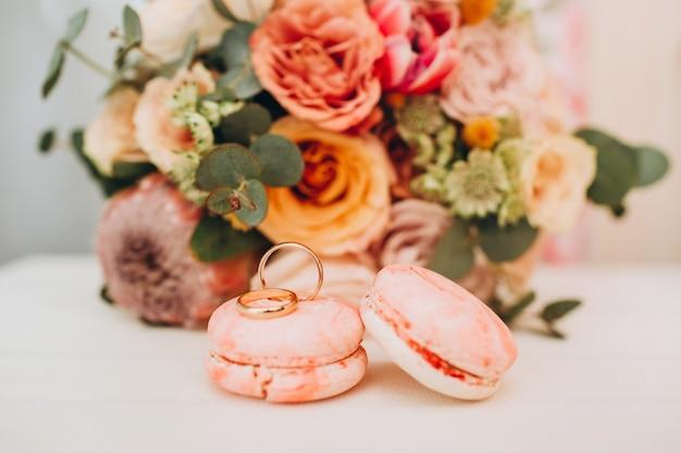 Hochzeitsstrauß in herbstfarben, eheringen und makronen auf einem weißen tisch.