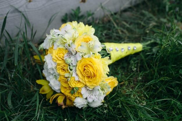 Hochzeitsstrauß mit gelben rosen, die auf dem gras liegen
