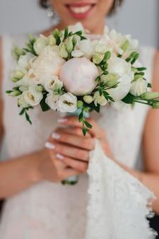 Hochzeitsstrauß mit pfingstrosen in den händen der braut