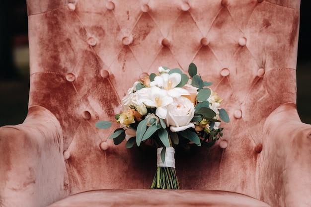 Hochzeitsstrauß mit rosen auf dem tisch und einem boutonniere