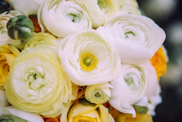 Hochzeitsstrauß mit weißen nelken und ranunkeln. zartes bouquet in gelb und weiß. eukalyptusblätter.