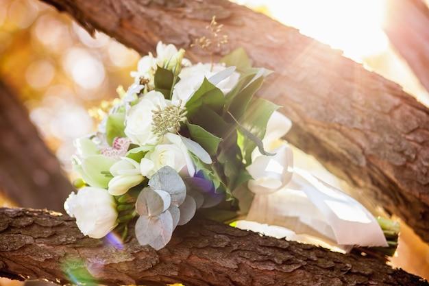 Hochzeitsstrauß mit weißen rosen auf holzoberfläche