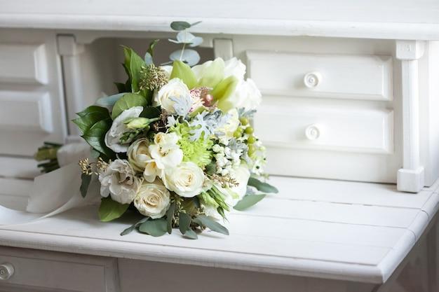 Hochzeitsstrauß mit weißen rosen auf weißer holzoberfläche