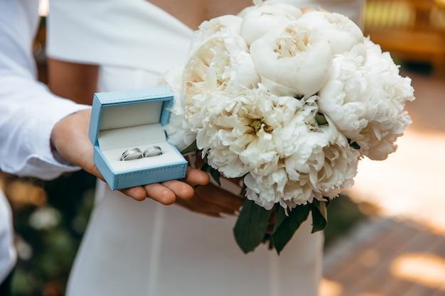 Hochzeitsstrauß und eheringe in händen