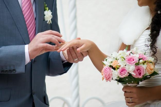 Hochzeitsstrauß und hände mit ringen