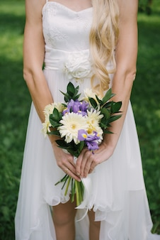 Hochzeitsstrauß von lila lila iris und hellgelben gerbera mit zweigen von grünen blättern