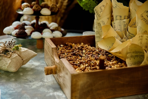 Hochzeitssüßigkeiten und nüsse auf tisch im rustikalen stil